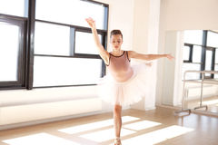 Ballerina in Arabesque Position in Dance Studio Royalty Free Stock Photography