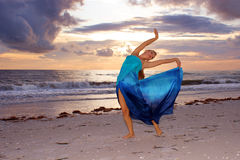 Ballerina arching back. A beautiful blonde ballerina is arching back with her arms up on the beach as the sun sets looking at you the viewer and smiling Stock Photos