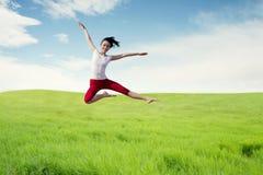 Ballerina asiatica della donna che fa un grande salto sul prato immagini stock libere da diritti