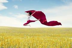 Ballerina asiatica della donna che tiene tessuto rosso che fa un grande salto sul prato fotografie stock