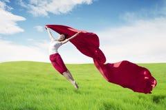 Ballerina asiatica della donna che tiene tessuto rosso che fa un grande salto sul prato immagini stock