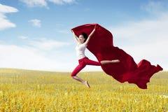 Ballerina asiatica della donna che tiene tessuto rosso che fa un grande salto sul prato fotografia stock