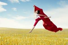 Ballerina asiatica della donna che tiene tessuto rosso che fa un grande salto sul prato fotografia stock libera da diritti