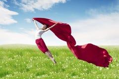 Ballerina asiatica della donna che tiene tessuto rosso che fa un grande salto sul prato del fiore fotografie stock libere da diritti