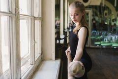 Ballerina attraente che si scalda nella classe di balletto Fotografia Stock
