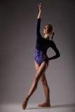 Ballerina in attrezzatura blu che posa, giovane bella donna esile sul fondo grigio dello studio Fotografia Stock Libera da Diritti
