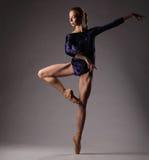 Ballerina in attrezzatura blu che posa sulle dita del piede, fondo dello studio Fotografie Stock Libere da Diritti