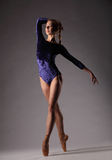 Ballerina in attrezzatura blu che posa sulle dita del piede, fondo grigio dello studio Fotografia Stock Libera da Diritti