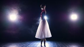 A ballerina balances and turns in the dark. stock video
