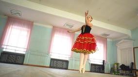Ballerina in a ballet hall. Arabesque. Classical Ballet dancer side view. Beautiful graceful ballerine in black practice ballet position near large window in stock footage