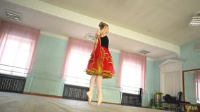 Ballerina in a ballet hall. Arabesque. Classical Ballet dancer side view. Beautiful graceful ballerine in black practice ballet position near large window in stock video