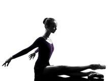 Ballerina-Balletttänzer der jungen Frau, der silho aufwärmend ausdehnt Stockbild