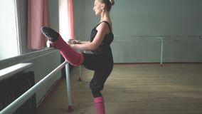 Ballerina at the Barre. Ballerina standing on poite at barre in ballet class stock video