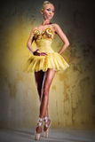 Ballerina. Beautiful ballerina in yellow tutu on point posing over obsolete wall Royalty Free Stock Images