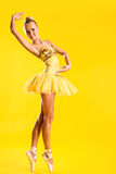 Ballerina. Beautiful ballerina in yellow tutu on point posing over yellow background Royalty Free Stock Photography