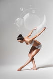 Ballerina bending down with soap bubbles Royalty Free Stock Photos