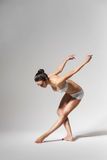 Ballerina bending down Stock Images