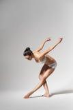 Ballerina bending down Stock Images
