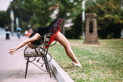 Ballerina bends back through the bench Royalty Free Stock Images