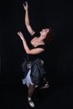 Ballerina in black dress over dark background Stock Images