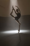 Ballerina in black leotard. Young ballerina posing during her training in the dark dance hall. She standing on one leg with raised hands and other leg. Light Stock Image