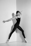 Ballerina in black outfit posing on pointe shoes, studio background. Royalty Free Stock Images
