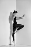 Ballerina in black outfit posing on pointe shoes, studio background. Royalty Free Stock Photos