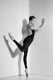 Ballerina in black outfit posing on pointe shoes, studio background. Stock Image