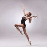 Ballerina in black outfit posing on toes Stock Photos