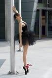 Ballerina in black tutu near a pole stock image