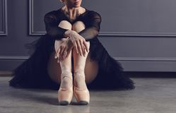 Ballerina in a black tutu sitting on the floor on a black background. Concept ballet dancing dancer royalty free stock image