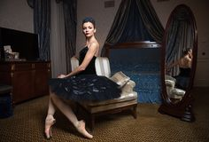 Ballerina in black tutu sitting in front of mirror Stock Photos