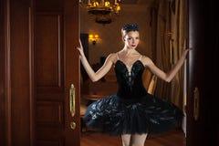 Ballerina in black tutu standing in doorway Stock Images