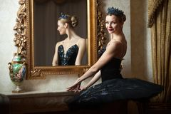 Ballerina in black tutu standing front of mirror Stock Image