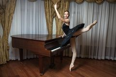 Ballerina in black tutu standing on pointes Stock Photos