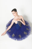 Ballerina in Blue. Profile of a Ballerina wearing a blue tutu sitting down stock photography