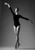 Ballerina in blue outfit posing on toes, studio shot. Grayscale image. royalty free stock image