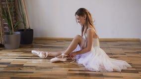 Ballerina cambiare le loro scarpe in scarpe di balletto speciali, scarpe bianche del pointe, pizzo con i nastri di balletto Giova archivi video