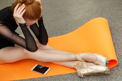 Ballerina and cell phone. Sad ballerina is sitting on a gym mat. A cell phone is lying next to her. The missed call stock photo