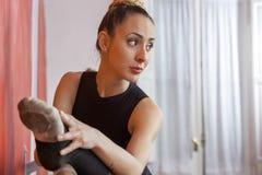 Ballerina che allunga la sua gamba nello studio di ballo Fotografie Stock