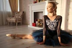 Ballerina che allunga scaldarsi nell'interno domestico, spaccatura sul pavimento Fotografie Stock Libere da Diritti