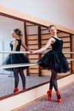 Ballerina che indossa ballo nero del tutu nello specchio nel corridoio di addestramento Immagini Stock