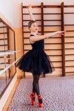 Ballerina che indossa ballo nero del tutu vicino allo specchio nel corridoio di addestramento Immagine Stock