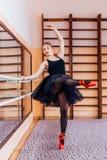 Ballerina che porta tutu nero che fa esercizio nel corridoio di addestramento Immagine Stock