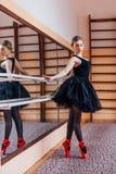 Ballerina che porta tutu nero che fa esercizio nel corridoio di addestramento Fotografie Stock Libere da Diritti