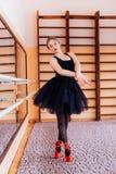 Ballerina che porta tutu nero che fa esercizio nel corridoio di addestramento Fotografia Stock Libera da Diritti
