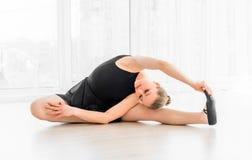 Ballerina che si siede sulla punta dei piedi sul pavimento Immagini Stock