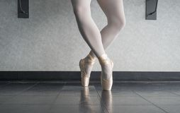 Ballerina dancer in the ballet studio en pointe in releve fourth position. In ballet class stock image