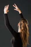 Ballerina dancer posing with her hands on a dark Royalty Free Stock Image