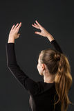 Ballerina dancer posing with her hands on a dark Stock Photos